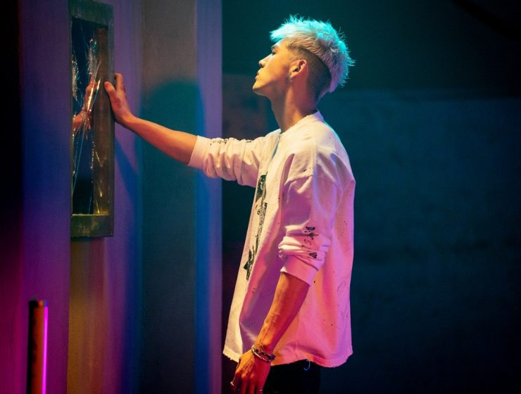 """BM of KARD stands at a smashed mirror looking into it during his """"Broken Me"""" Music video produced by 8Pex and Vive studios"""